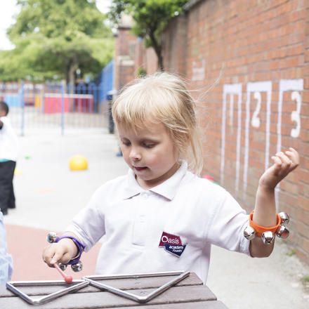 A pupil plays with musical instruments