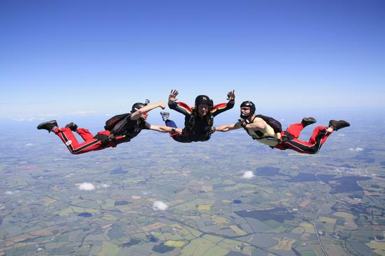 Three skydivers in free fall