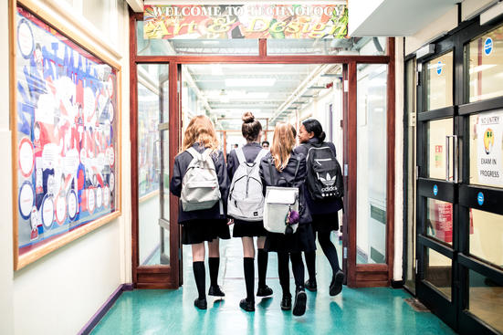 Four pupils walking down a school corridor, backs to the camera