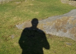 The author's shadow cast on a grassy hillside overlooking moorland