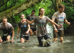 Runners wading through a stream as part of the Wolf Run