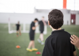 Pupil on a school sports field, facing away from the camera and looking at other pupils playing football