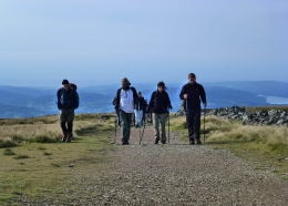 A group of walkers hike along a gravel path