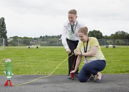 A teacher and student test a air-pressured rocket