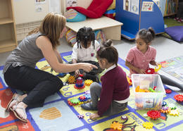 A teacher sits with her pupils playing with toys