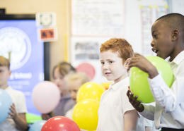 Pupils in a primary classroom playing with balloons.