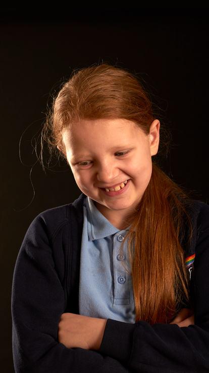 A primary pupil smiling and looking down.