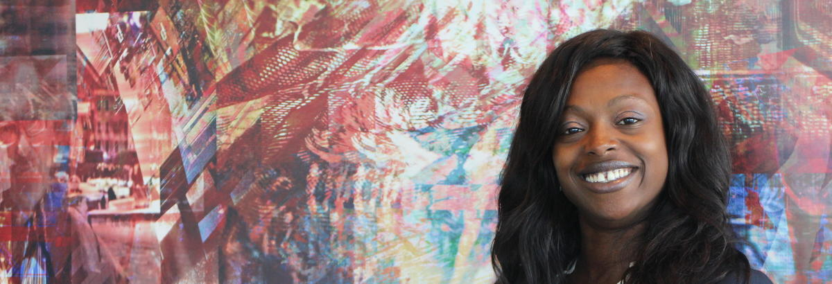 A CELP participant smiles in front of an abstract painting