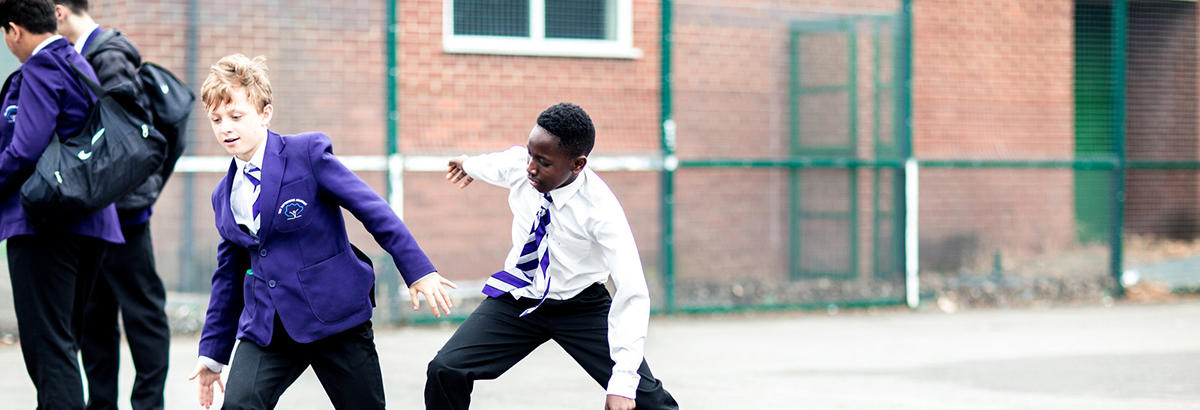 Two pupils play football