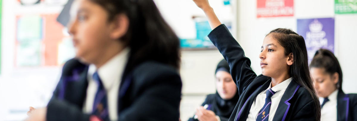 A pupil holds their hand up