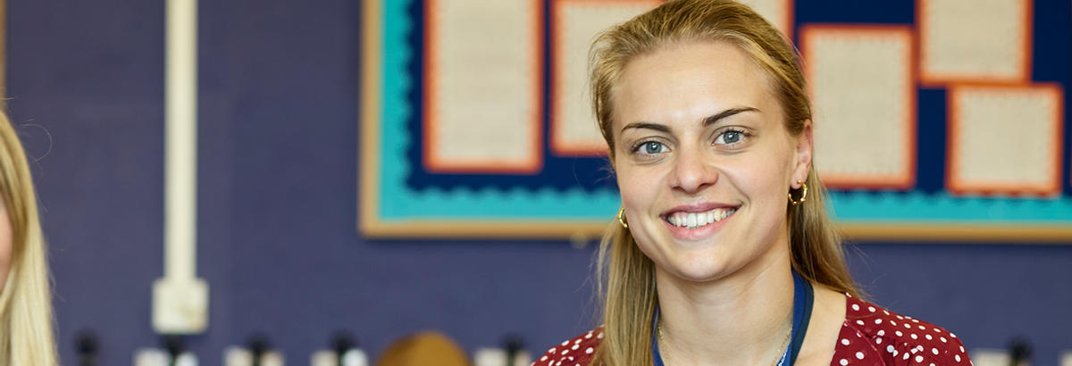 Steph Rees sits in a classroom and smiles at the camera