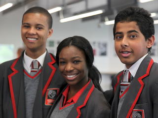 three students in uniform smiling at camera