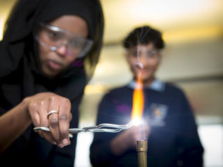 Girl holding something in a bunsen burner flame with metal tongs