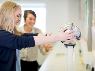 girl in a physics lesson with her hands on a van de graaff generator