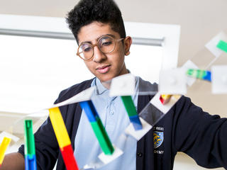 male student wearing glasses holding up a DNA double helix model