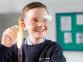 young student holding something in a bunsen burner wearing safety goggles and smiling