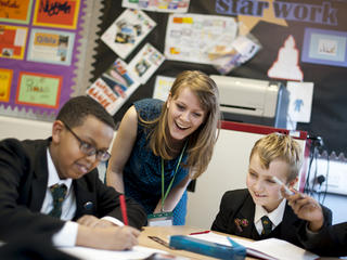 Teacher helps pupils at their desk