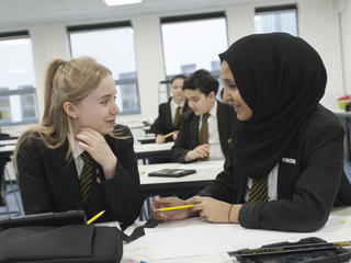 Two pupils in discussion at desk