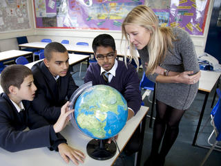 Teacher and three pupils look at globe