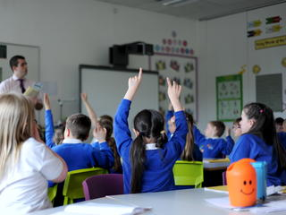 Classroom with pupils raising their hands