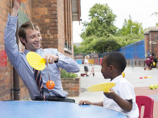 Teacher and pupil with table tennis rackets
