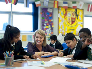 teacher and pupils at desk smiling
