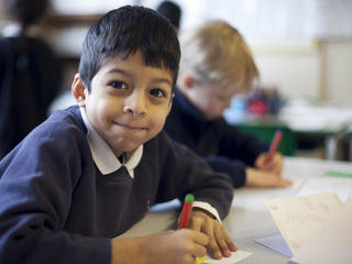 Young pupil seating at his desk writing