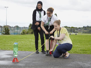 Two girl pupils conducting experiment outside with their teacher
