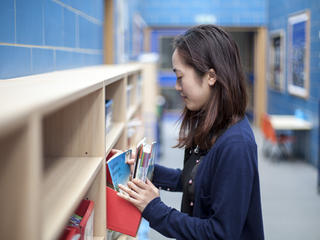 A Teach First trainee looking for a workbook in a shelf in school.