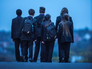 A group of pupils facing away from the camera at dusk, looking towards the horizon.