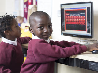 Pupil smiling to camera while in a computing lesson.