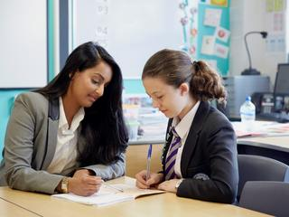 Teacher with girl at desk with work