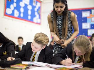 Teacher stands over pupils working