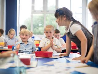 Pupils standing up and sitting down around table