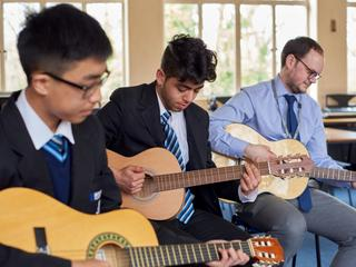 Two students and teacher playing acoustic guitars