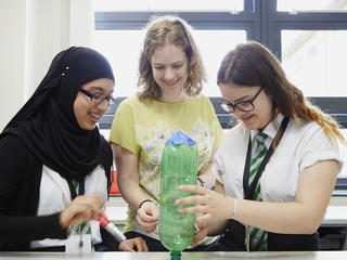 Teacher and pupils engaged in a science lesson with bottle