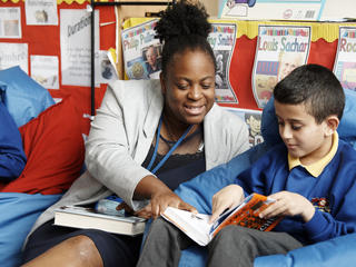 Teach First trainee and pupil reading a book