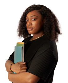 A woman looking to camera while holding a stack of exercise books..