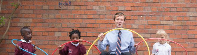 male teacher sits with three primary years students. all hold hula hoops
