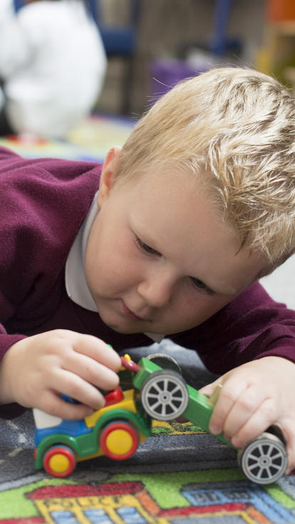 Young boy plays with cars